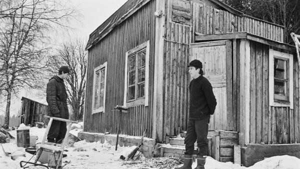 Nuorempi ja vanhempi mies seisovat vanhan puutalon edustalla, luminen maa ja edustalla potkukelkka
