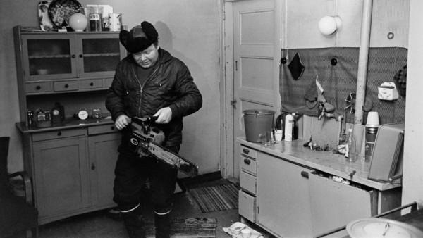 Mies ulkovaatteissa keittiössä moottorisaha kädessä