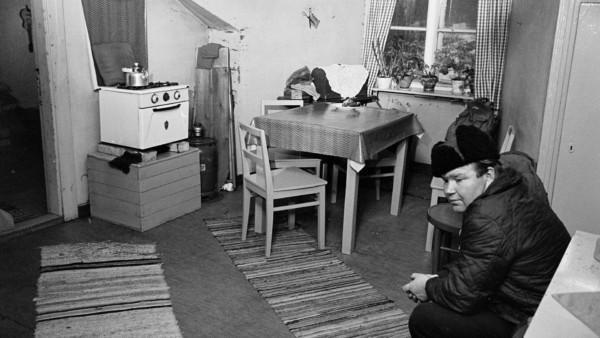 Mies istuu ulkovaatteissa keittiön nurkassa, lattialla räsymatot