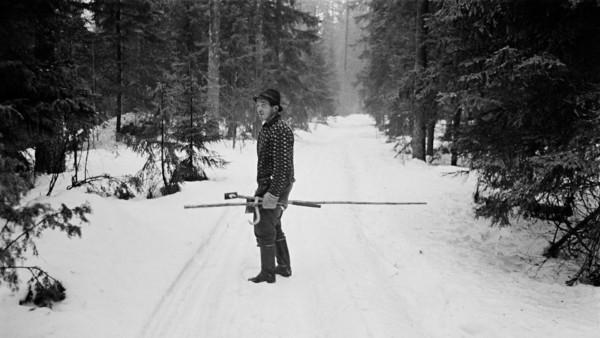 Lumisella metsätiellä vanha mies hattu päässä kädessään puutyökaluja