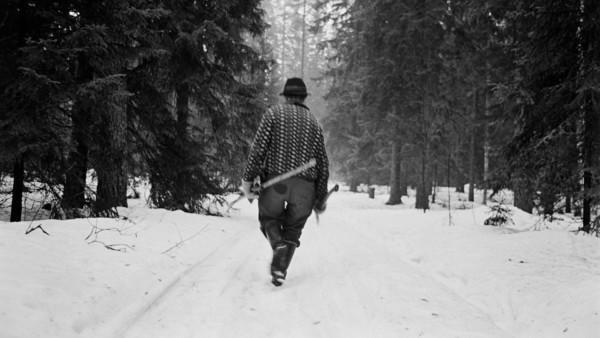 Lumisella metsätiellä hattupäinen mies kävelemässä poispäin puutyökalut kädessä