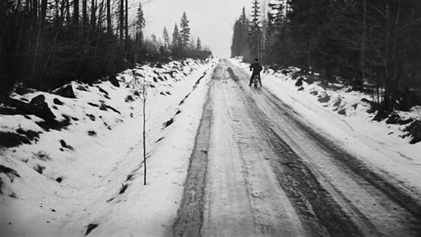 Mies ajaa mopoa lumisella metsätiellä