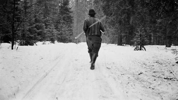 Lumisella metsätiellä hattupäinen mies kävelemässä ripeästi poispäin puutyökalut kainaloissa heiluen