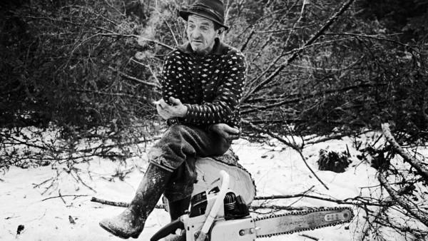 Vanha hattupäinen mies istuu lumisessa metsässä kaatamansa puunrungon päällä polttaen tupakkaa, edustalla moottorisaha
