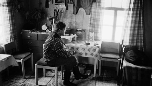 Vanha mies tuvassa tuijottamassa istuen ikkunasta, ikkunasta sarastaa valoa
