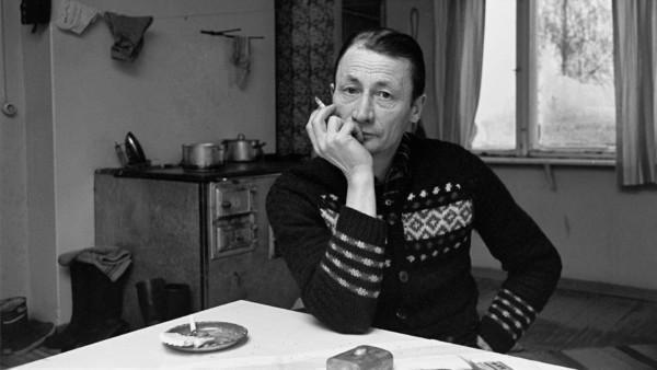Mies villapaidassa nojaa kyynärpäällään pöytää vasten, tupakka sormien välissä, taustalla puuhella