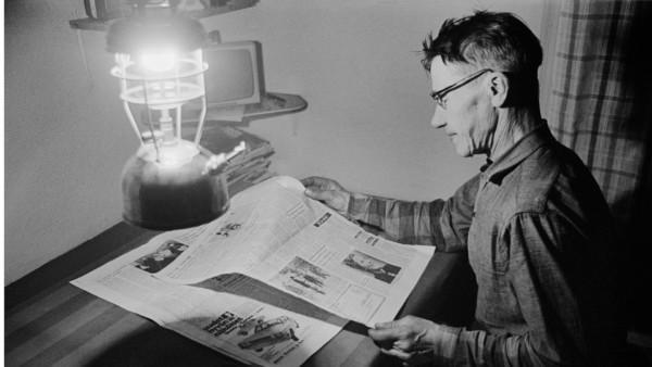 Vanha mies lukemassa pöydän ääressä sanomalehteä öljylampun valossa