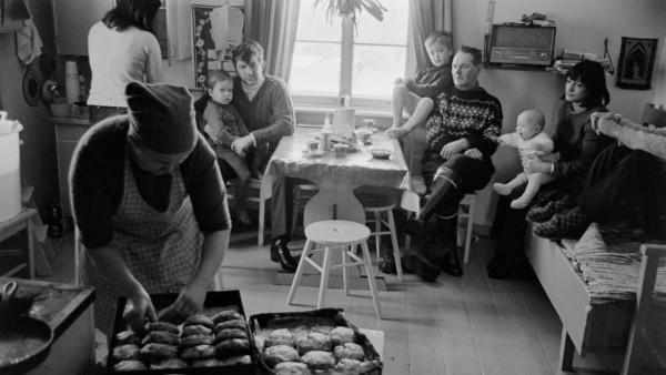 Etualalla muori asettelemassa leivonnaisia, tuvassa taustalla viisi aikuista, kaksi lasta ja vauva pöydän ääressä