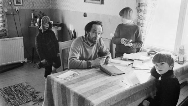 Keittiön pöydän ääressä mies ja kaksi lasta, pöydällä papereita, taustalla lapsi ulkovaatteissa