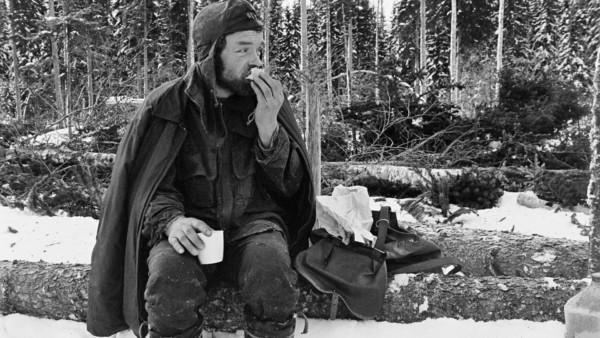 Lumisessa metsässä mies talvivaatteissa evästauolla puunrungon päällä istuen, taustalla kaadettuja puita ja metsää