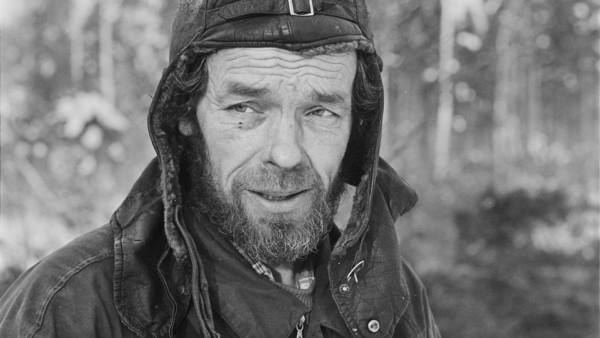 Lähikuva parrakkaasta miehestä nahkalakissa, taustalla metsää