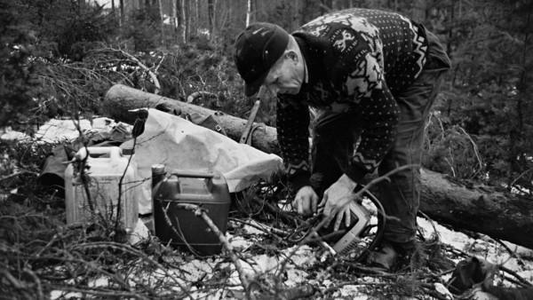 Mies asettelee maahan moottorisahan ja kanistereita lumisessa metsässä