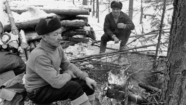 Kaksi hattupäistä miestä istumassa nuotion ääressä, taustalla pino puun ruokoja ja luminen metsä