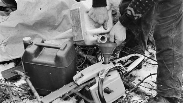 Mies tankkaa moottorisahaan bensiiniä kanisterista, taustalla pressu
