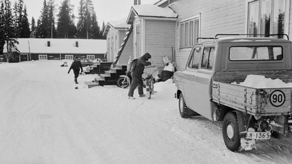 Suuren puutalon edessä mies nousemassa mopon kyytiin, toinen mies kävelemässä taustalla. Maassa lunta, edustalla lava-auto, taustalla piharakennus ja metsää