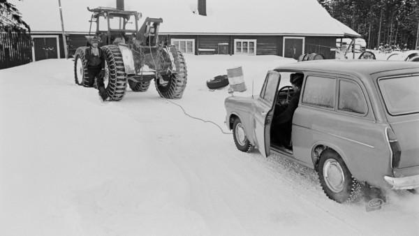 Lumisella pihalla traktori, jolla hinattu ford-henkilöautoa. Traktorissa lumiketjut renkaissa ja vierellä nainen, fordin ratissa hattupäinen mies. Taustalla piharakennus ja metsää