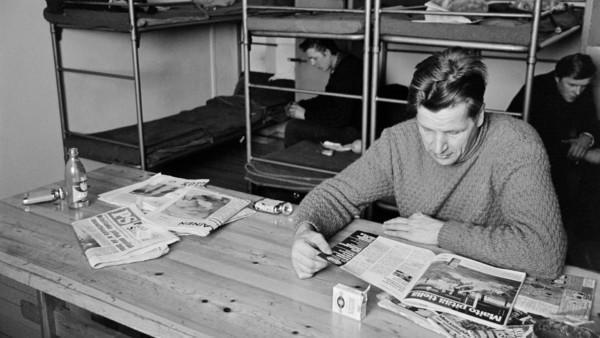 Etualalla mies villapaidassa lukemassa lehteä puupöydän ääressä, taustalla kaksi miestä istumassa kerrossängyillä