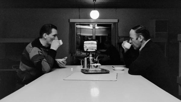 Kaksi miestä juomassa kahvia valkoisen pöydän ääressä, taustalla ikkuna ja televisio