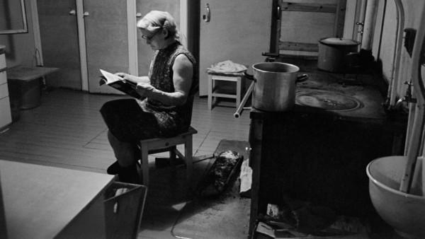 Nainen tuvassa puuhellan edessä lukemassa lehteä