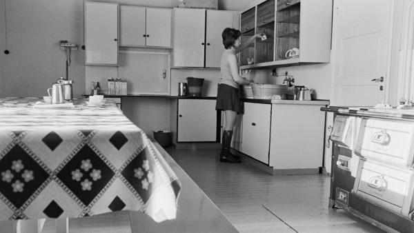 Nainen tiskaamassa keittiössä hameessa ja saapikkaissa