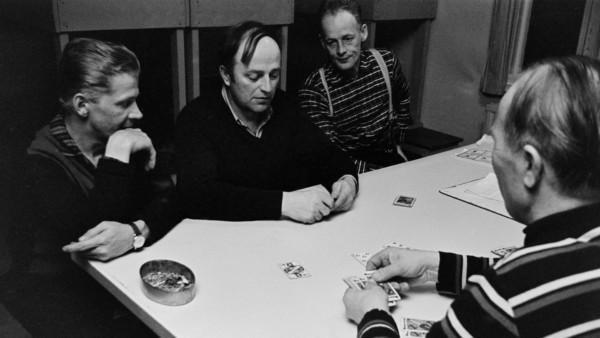 Neljä keski-ikäistä miestä pelaamassa korttia pöydän ääressä