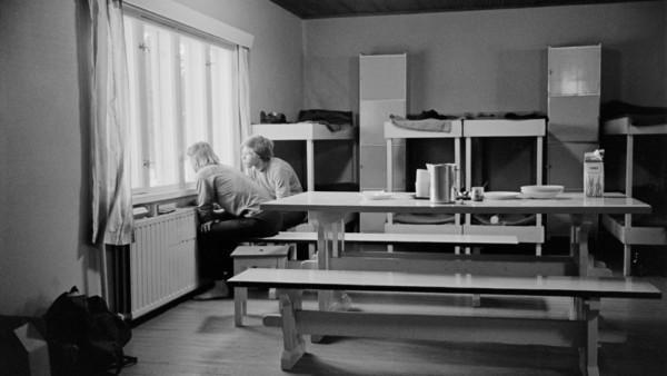 Kaksi miestä katsomassa ikkunasta istuen, huoneessa pirtinpöytä ja neljä kerrossänkyä