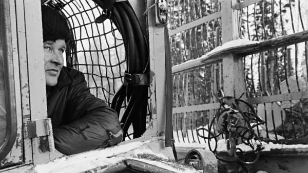 Mies katsomassa traktorin ikkunasta, taustalla talvista metsää