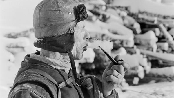 Lähikuva miehestä talvivaatteissa polttamassa piippua, taustalla puunrunkopino ja lunta