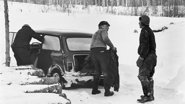 Kolme miestä auton ympärillä, yksi mies takakontilla, taustalla metsää ja lunta