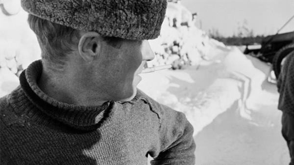 Lähikuva hattupäisestä miehestä savuke suussa, taustalla lumen peittämä runkopino