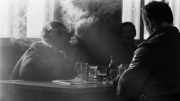 Neljä miestä kapakassa pöydän ääressä, yksi polttaa savuketta, pöydällä olutpullo ja laseja