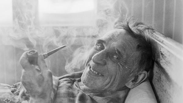 Lähikuva makuullaan olevasta hymyilevästä vanhasta miehestä, joka polttaa piippua, taustalla ikkuna