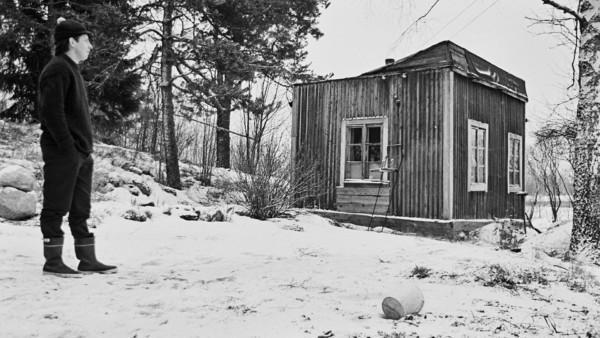 Nuori mies pienen mökin edustalla, taustalla luminen maalaismaisema