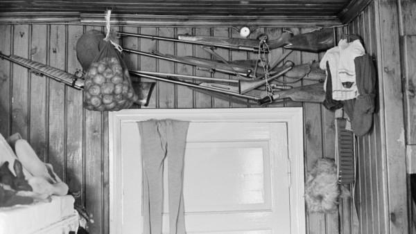 Vaalean oven päällä riippuu housut, seinällä oven yläpuolella ripustettuna aseita, vaatteita ja perunoita pussissa