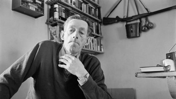 Lähikuva miehestä neuleessa ja kauluspaidassa, taustalla huoneessa kirjahylly, seinälle ripustettuna ase ja kiikarit
