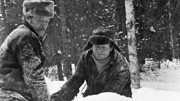 Lähikuva kahdesta miehestä talvivaatteissaan uurastamassa, taustalla luminen metsä
