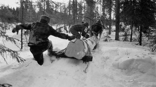 Kaksi miestä lumisessa metsässä auttamassa hevosta vetämään suurta puun runkoa