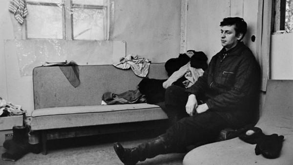 Keski-ikäinen mies istuu väsyneenä vaatimattomassa olohuoneessa, ikkunassa läpinäkyvä pressu, sohvalla vaatteita