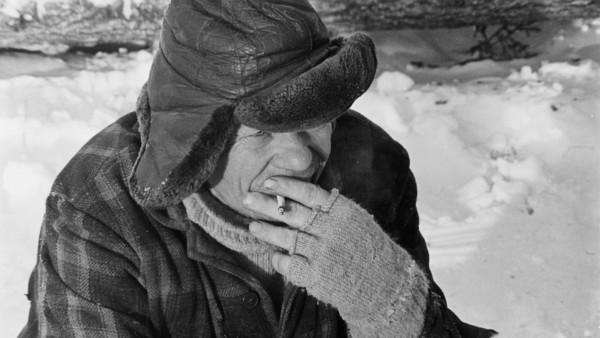 Lähikuvassa vanha mies talvivaatteissa polttamassa savuketta, taustalla lunta