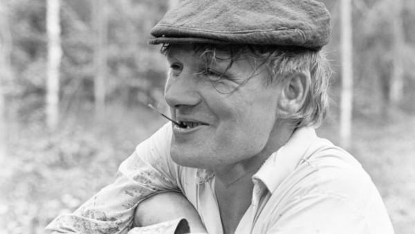Lähikuva nauravasta hattupäisestä miehestä, tautalla metsää