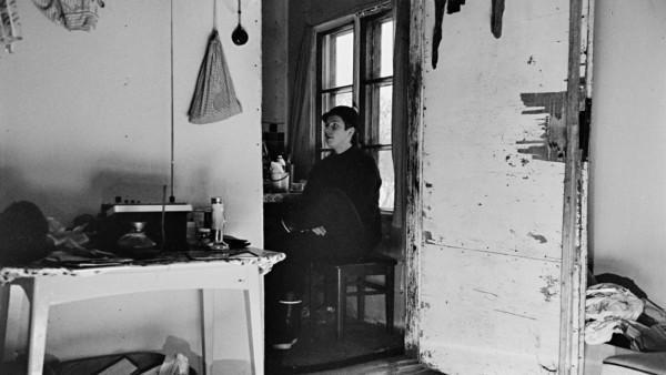 Huoneen avoimesta ovesta näkyy nuori mies istumassa ikkunan edustalla