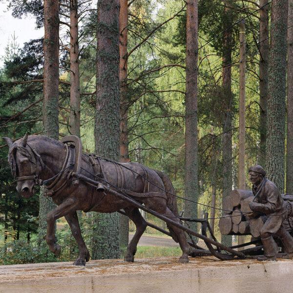 Pronssinen, oikean kokoinen patsas tukkikuormaa vetävästä hevosesta ja ajurista.