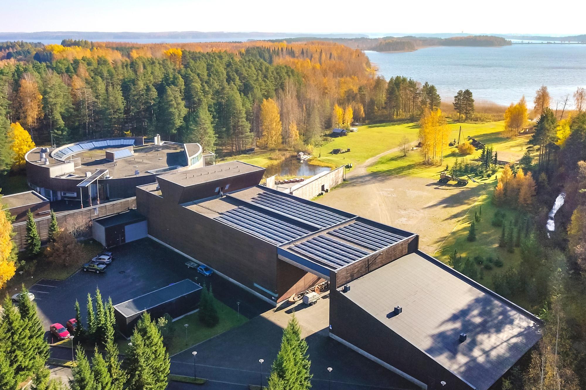Ilmakuva Luston rakennuksesta syksyllä, taustalla järvenselkä.