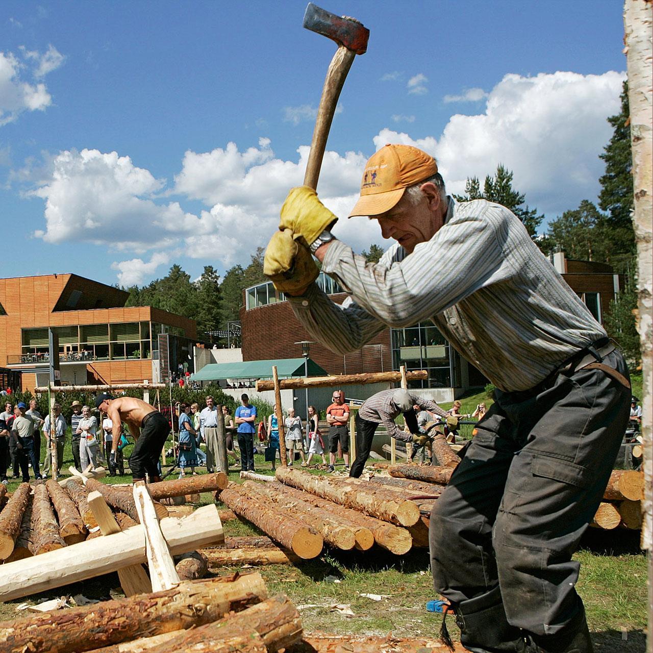 Ikämies hakkaa kirveellä puita Luston pihalla.