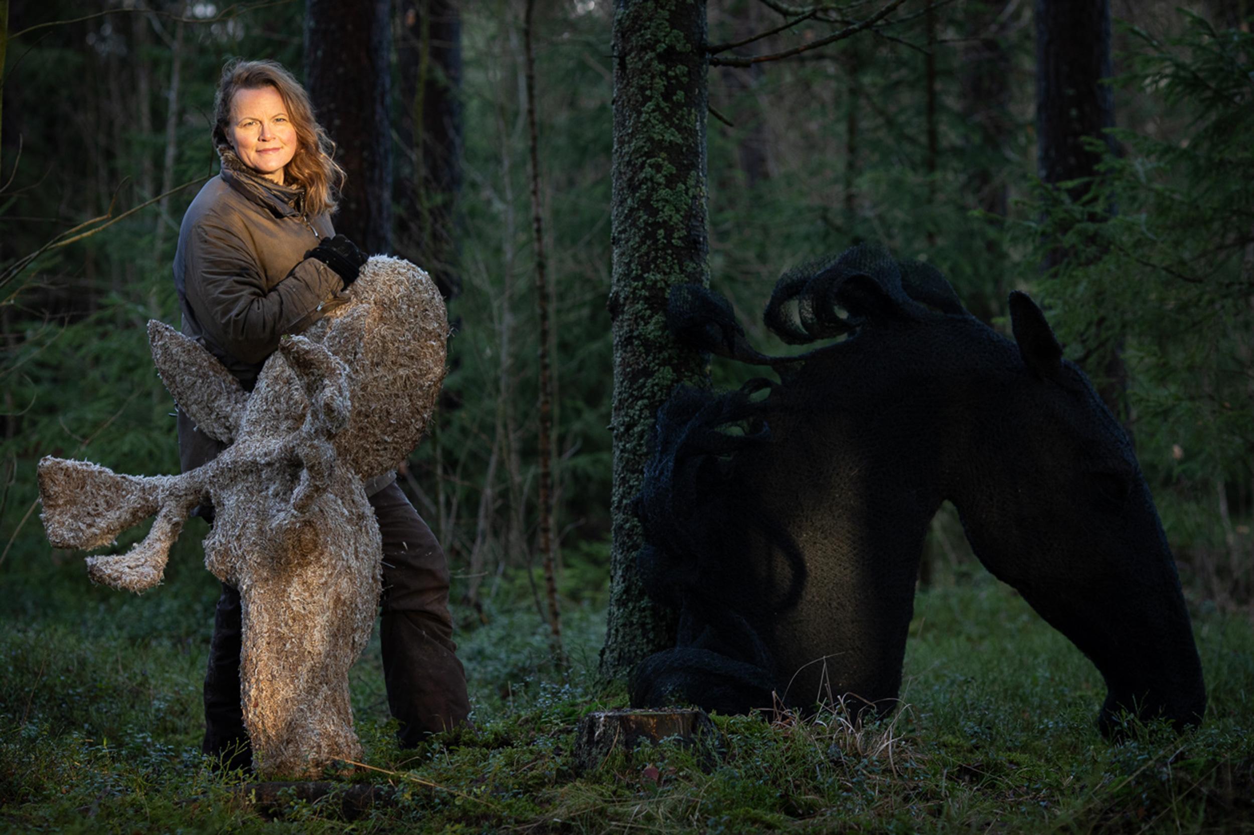 Tummassa metsässä seisoo nainen, joka katsoo kameraan ja nojaa puukuitumateriaalista tehtyn hirvenpäähän. Taustalla puuta vasten nojaa musta, verkkomaisesta materiaalista tehty hevosenpää.