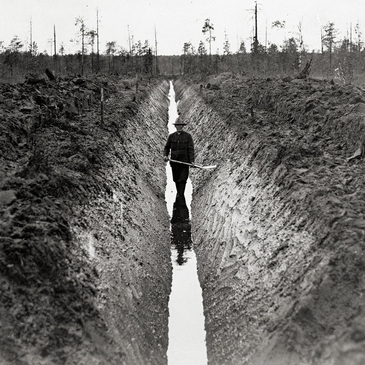 Työmies seisoo kaivamansa miehensyvyisen ojan pohjalla hattu päässä ja lapio käsissään.