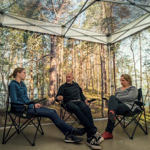 Kolme ihmistä keskustelee teltassa, johon on painettu metsämaisema.