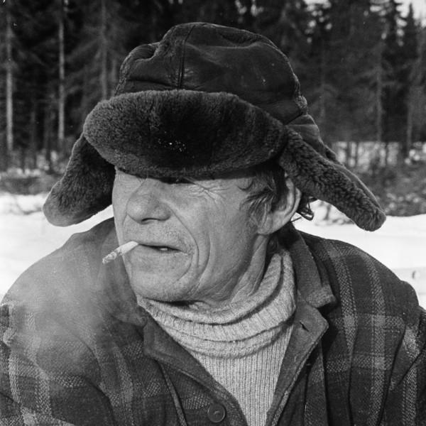 Metsätyömies tupakkatauolla, karvalakki päässä.