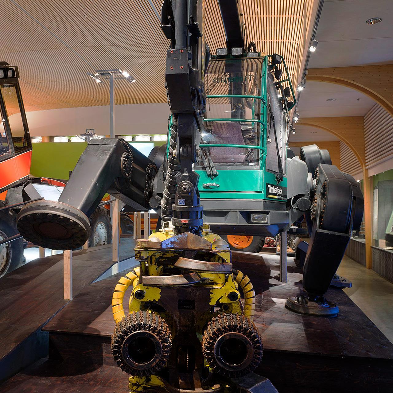 Kävelevä metsäkone Plusjack Luston Koneaika-näyttelyssä. Etualalla koura, sen takana itse kone yksi jalka ilmaan nostettuna.