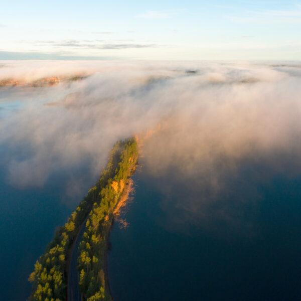 Ilmakuva Punkaharjun järvimaisemasta. Etualalla aamuauringossa harju joka peittyy yläosastaan aamusumuun.